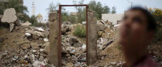 A Palestinian teen stands next to the frame of a destroyed house doorway, on which British street artist Banksy painted an image of a goddess holding her head in her hand, after the door with the painted image was sold in the northern Gaza Strip