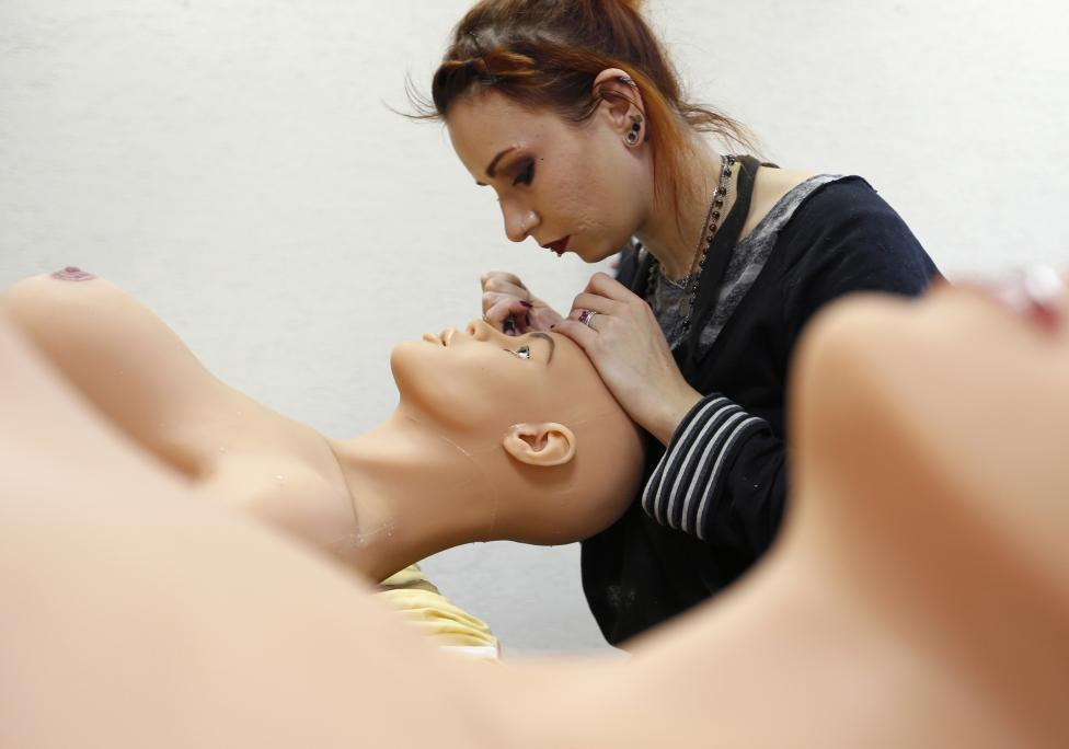 Raphaela, an employee at the Dreamdoll company, works on the makeup of a silicone dream doll at their workshop in Duppigheim near Strasbourg