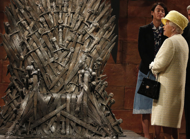 Britain's Queen Elizabeth looks at the Iron Throne as she meets members of the cast on the set of the television show Game of Thrones in the Titanic Quarter of Belfast