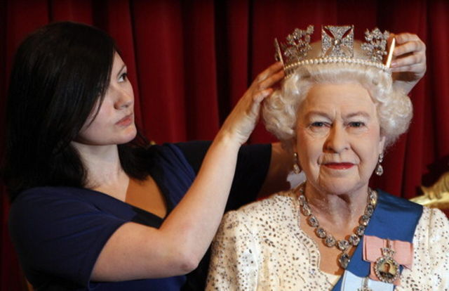 Madame Tussauds employee Keeley Scothern poses with a new figure of Britan's Queen Elizabeth, produced in honour of her Diamond Jubilee in London