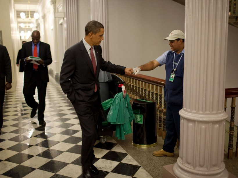 President Barack Obama fist-bumps custodian Lawrence Lipscomb in the Eisenhower Executive Office Building following the opening session of the White House Forum on Jobs and Economic Growth, Dec. 3, 2009. (Official White House Photo by Pete Souza) This official White House photograph is being made available only for publication by news organizations and/or for personal use printing by the subject(s) of the photograph. The photograph may not be manipulated in any way and may not be used in commercial or political materials, advertisements, emails, products, promotions that in any way suggests approval or endorsement of the President, the First Family, or the White House.
