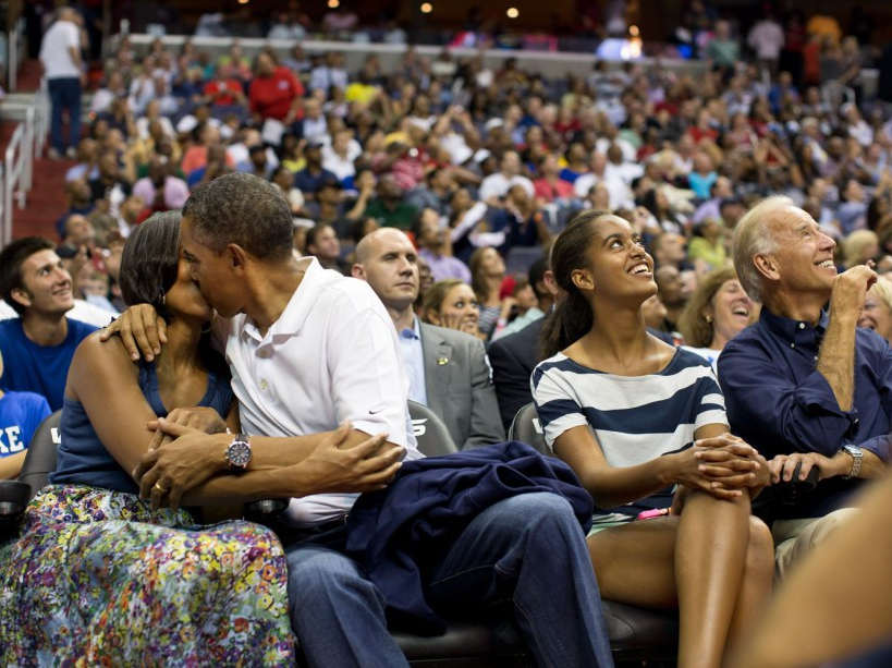 "President Barack Obama kisses First Lady Michelle Obama for the ""Kiss Cam"" while attending the U.S. Men's Olympic basketball team's game against Brazil at the Verizon Center in Washington, D.C., July 16, 2012. Vice President Joe Biden and Malia Obama look up at the jumbotron. (Official White House Photo by Pete Souza) This official White House photograph is being made available only for publication by news organizations and/or for personal use printing by the subject(s) of the photograph. The photograph may not be manipulated in any way and may not be used in commercial or political materials, advertisements, emails, products, promotions that in any way suggests approval or endorsement of the President, the First Family, or the White House.Ê"