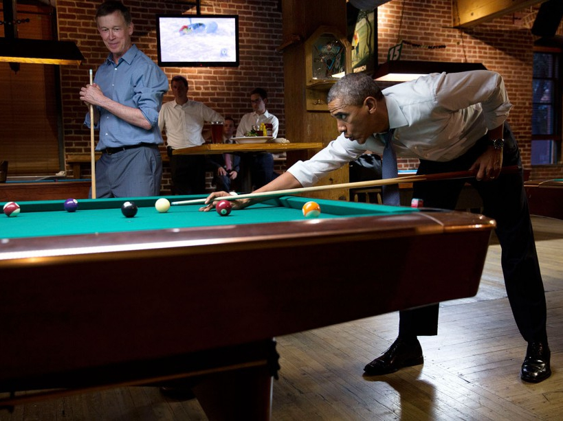President Barack Obama whistles along to the music as he shoots pool with Gov. John Hickenlooper, D-Colo. in Denver, Colo., July 8, 2014. (Official White House Photo by Pete Souza) This official White House photograph is being made available only for publication by news organizations and/or for personal use printing by the subject(s) of the photograph. The photograph may not be manipulated in any way and may not be used in commercial or political materials, advertisements, emails, products, promotions that in any way suggests approval or endorsement of the President, the First Family, or the White House.