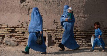 Afghan women walk with their children through the old quarters of Herat on September 20, 2016.  / AFP PHOTO / AREF KARIMI