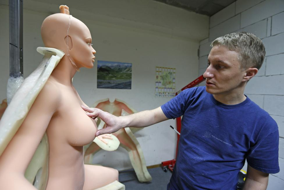 Eric, an employee at the Dreamdoll company, inspects a silicone dream doll as he removes it from a mold at their workshop in Duppigheim near Strasbourg
