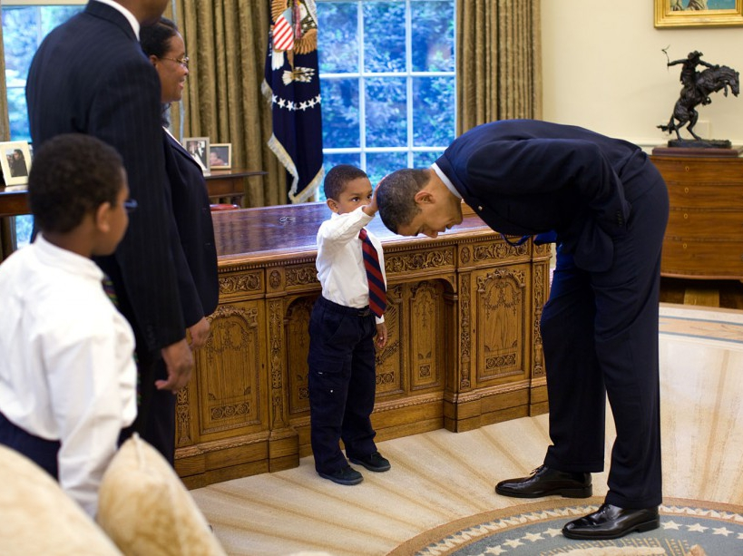 """May 8, 2009 """"A temporary White House staffer, Carlton Philadelphia, brought his family to the Oval Office for a farewell photo with President Obama. Carlton's son softly told the President he had just gotten a haircut like President Obama, and asked if he could feel the President's head to see if it felt the same as his."""" (Official White House photo by Pete Souza) This official White House photograph is being made available only for publication by news organizations and/or for personal use printing by the subject(s) of the photograph. The photograph may not be manipulated in any way and may not be used in commercial or political materials, advertisements, emails, products, promotions that in any way suggests approval or endorsement of the President, the First Family, or the White House."""