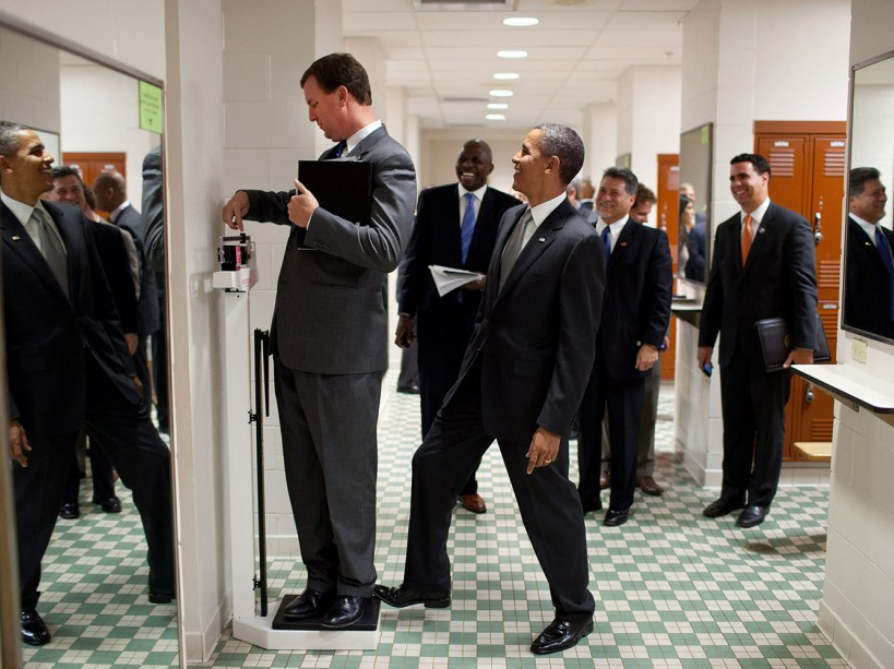 """Aug. 8, 2010 """"We were walking through a locker room at the University of Texas when White House Trip Director Marvin Nicholson stopped to weigh himself on a scale. Unbeknownst to him, the President was stepping on the back of the scale, as Marvin continued to slide the scale lever. Everyone but Marvin was in on the joke."""" (Official White House Photo by Pete Souza) This official White House photograph is being made available only for publication by news organizations and/or for personal use printing by the subject(s) of the photograph. The photograph may not be manipulated in any way and may not be used in commercial or political materials, advertisements, emails, products, promotions that in any way suggests approval or endorsement of the President, the First Family, or the White House."""